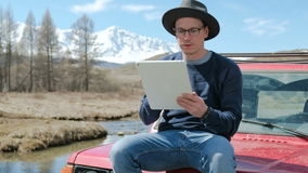Young hipster fashion guy with computer tablet sitting next his car during road trip. 20s 4k. Young hipster fashion guy with computer tablet sitting next his car stock video footage