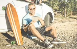 Young hipster fashion guy working remote on table at car trip. Young hipster fashion guy working remote on computer tablet sitting at car on road trip - New Stock Images