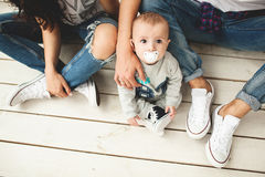 Young hipster father, mother and baby boy on wooden floor Stock Photos