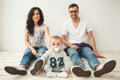 Young hipster father, mother and baby boy on wooden floor Royalty Free Stock Photo