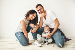 Young hipster father, mother and baby boy on wooden floor Stock Image