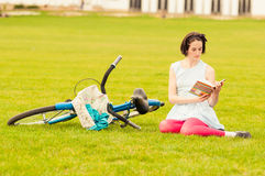 Young hipster female reading a book outside in the park Royalty Free Stock Photos