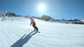 Young hipster female snowboarder on sunny slope. Slow motion shot of young athlete or female snowboarder in hipster outfit, enjoy time outdoors in nature, ride stock footage