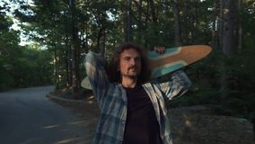 Young hipster in the forest, making fun with a longboard. Uses longboard as a guitar. Jumps like a rock star. Fun
