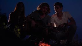 Young hipster friends chilling on beach playing guitar and singing with a fire and chatting in cozy summer evening. Happy hipster friends chilling on beach stock video footage