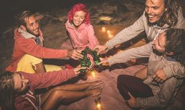 Young hipster friends having fun together at night beach party stock photography
