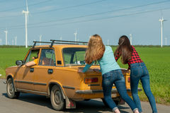 Young hipster friends on road trip on a car. Young hipster friends on road trip on a summers day. Engine break down.Two girls pushing a vintage car while men is Royalty Free Stock Images