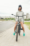 Young hipster girl with black bike. Looking at camera. Outdoor lifestyle portrait Royalty Free Stock Images