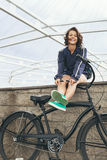 Young hipster girl with black bike Stock Photography