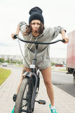 Young hipster girl with black bike. Young hipster girl on black bike making a face at camera. Outdoor lifestyle portrait Royalty Free Stock Photo
