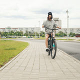 Young hipster girl with black bike Stock Images