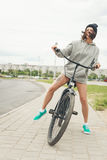 Young hipster girl with black bike Stock Photo