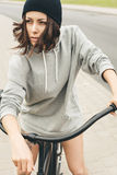 Young hipster girl with black bike Royalty Free Stock Photos