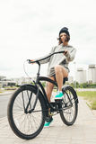 Young hipster girl with black bike Royalty Free Stock Image