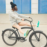 Young hipster girl with black bike. Young hipster girl riding black bike. Outdoor lifestyle portrait Royalty Free Stock Images