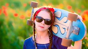 Young hipster girl with braids in sunglasses and a red sash on h Stock Photography