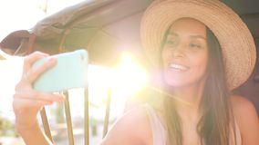Young Hipster Girl Doing Mobile Phone Selfie Photo in Bicycle Rickshaw Taxi with Amazing Lens Flare Sunset Effect on. Background. Thailand. 4K, Slowmotion stock footage