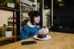 Young hipster girl eats tasty chocolate cake and drinking hot te Stock Photography