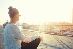 Young hipster girl enjoying sun and good warm day during her recreation time, woman relaxing outdoors after walking in the fresh a Royalty Free Stock Photography