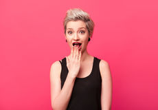 Young hipster girl going crazy, surprised emotions. Screaming and holding hand over mouth over pink color background. Short hairstyle modern woman amazed Stock Photo
