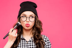 Young hipster girl having fun and going crazy, wearing glasses hat  bright make up. Pink urban background. The woman Royalty Free Stock Photo