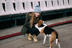 Young hipster girl with her pet estonian hound dog playing, junping and hugging and having fun outdoor at the old stadium. Stock Image