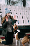 Young hipster girl with her pet estonian hound dog playing, junping and hugging and having fun outdoor at the old stadium. Royalty Free Stock Images