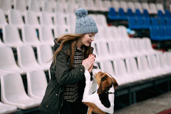 Young hipster girl with her pet estonian hound dog playing, junping and hugging and having fun outdoor at the old stadium. Young hipster girl with her pet Royalty Free Stock Images