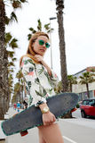 Young hipster girl holding skateboard while she standing on the lane lined with beautiful palm trees Royalty Free Stock Images
