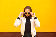 Young hipster girl holding yellow sunglasses on orange wall. Urban style Stock Photo