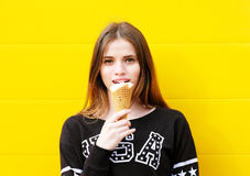 Young hipster girl with  ice-cream. Outdoor fashion portrait of young hipster girl with  ice-cream on yellow wall background Royalty Free Stock Photography