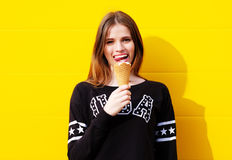 Young hipster girl with  ice-cream. Outdoor fashion portrait of young hipster girl with  ice-cream on yellow wall background Stock Photo