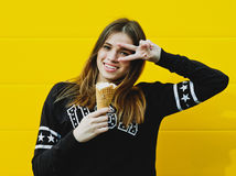 Young hipster girl with  ice-cream. Outdoor fashion portrait of young hipster girl with  ice-cream on yellow wall background Stock Photos
