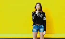 Young hipster girl with  ice-cream. Outdoor fashion portrait of young hipster girl with  ice-cream on yellow wall background Royalty Free Stock Images