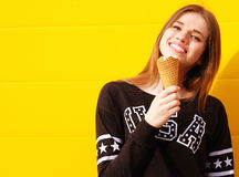 Young hipster girl with  ice-cream. Outdoor fashion portrait of young hipster girl with  ice-cream on yellow wall background Stock Photography