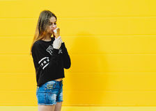 Young hipster girl with  ice-cream. Outdoor fashion portrait of young hipster girl with  ice-cream on yellow wall background Royalty Free Stock Image