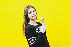 Young hipster girl with  ice-cream. Outdoor fashion portrait of young hipster girl with  ice-cream on yellow wall background Royalty Free Stock Photo