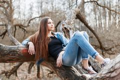 Young hipster girl with long hair and a denim jacket lying on a Stock Image