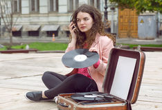 Young hipster girl with old vintage vinyl records listening music in city park Royalty Free Stock Image