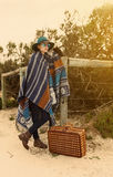 Young hipster girl in poncho with vintage suitcase Stock Images