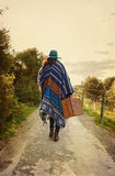 Young hipster girl in poncho with vintage suitcase Royalty Free Stock Photography