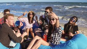 Young hipster girl recording a video or taking selfie of group of friends sitting on easychairs on the beach, playing. Guitar and singing on a summer evening stock footage