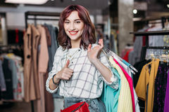 Young hipster girl smiling with thumb up in boutique. Clothes shopping concept Royalty Free Stock Photo