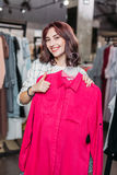 Young hipster girl smiling with thumb up in boutique. Clothes shopping concept Stock Images
