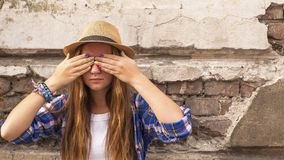 Young hipster girl standing in the street old town and closes his eyes his hands with colored nails. Royalty Free Stock Image