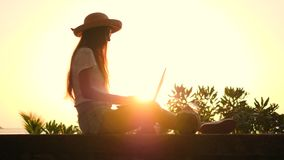 Young Hipster Girl in Straw Hat Sitting on the Beach and Typing on Laptop Keyboard with Beautiful Tropical Sunset on. Background. Remote Work on Travel Concept stock video