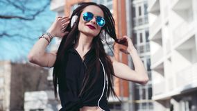 Young hipster girl in sunglasses listens to music on headphones, and happily dances to the rhythm from side to side in stock footage