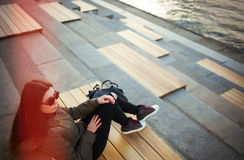Young hipster girl in sunglasses and parka sitting royalty free stock photography