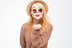 Young hipster girl in sunglasses send air kiss. Young fashionable attractive hipster girl in sunglasses and straw hat sends air kiss to camera. Nice playful and Stock Photography