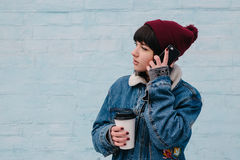Young hipster girl talking on the phone and drinking coffee. Young hipster girl in a blue denim jacket and hat, talking on the phone and drinking coffee on light Royalty Free Stock Photography